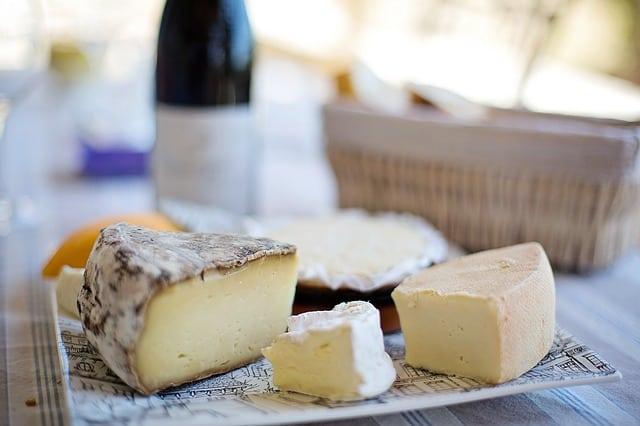 Tábua com queijos e vinho ao fundo