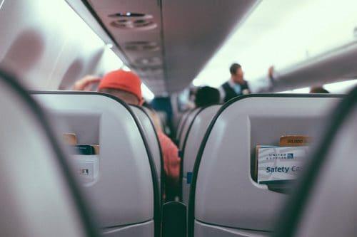 Poltronas e passageiros dentro de um avião