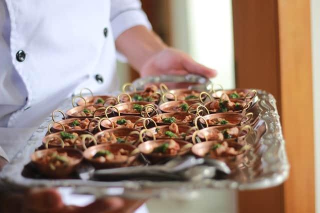 Chef segurando bandeja com pequenas porções de comida