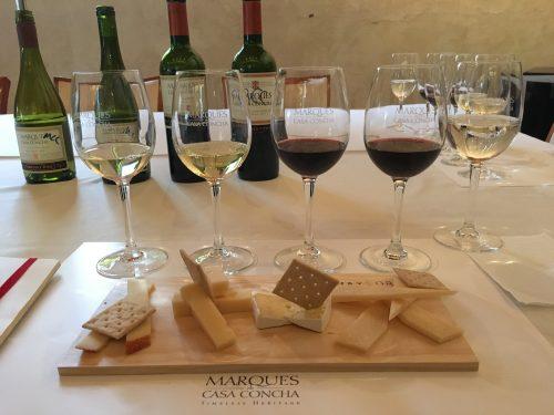 Tábua de queijos com vinhos ao fundo