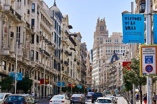 rua comercial com prédios e carros passando em madrid