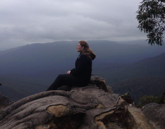 turista descansando em mirante com montanhas ao fundo