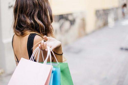Mulher com várias sacolas após compras