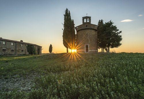 Campo gramado com igreja pequena e sol se pondo ao fundo