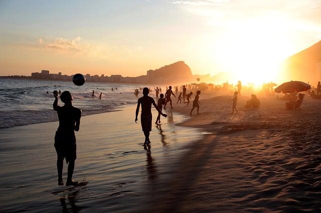pessoas em praia carioca durante o Pôr do sol