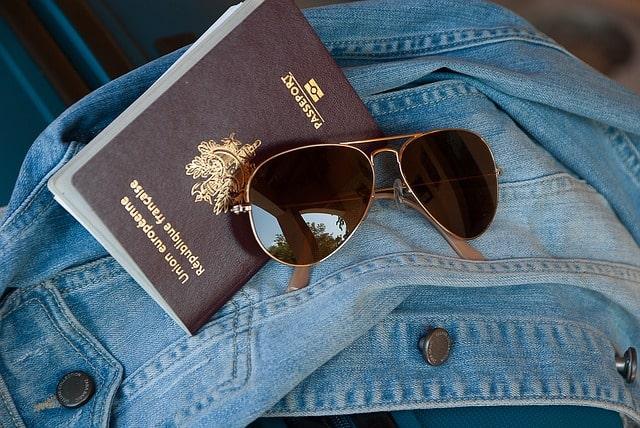 passaporte francês e óculos sobre blusa jeans
