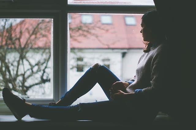 Mulher triste olhando para a janela