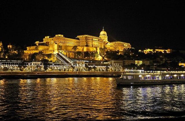 Castelo de Buda iluminado e barco passando no rio Danúbio