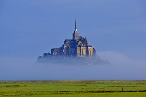 Campo verde com neblina e Monte Saint-Michel ao fundo