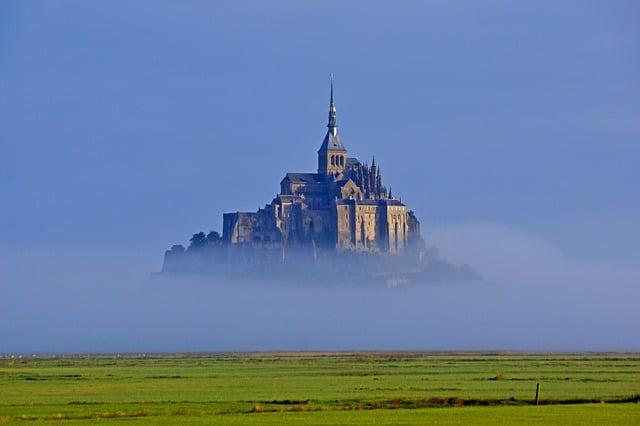 Campo verde com neblina e Mont Saint-Michel ao fundo