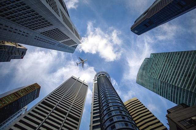 Avião voando entre prédios altos
