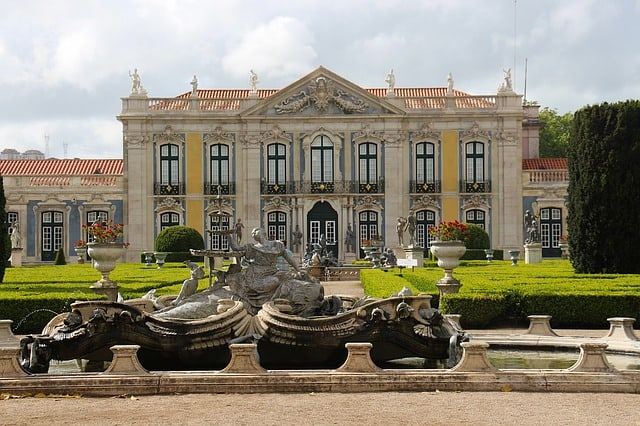 Palácio com dois andares, monumentos no topo e jardim na frente