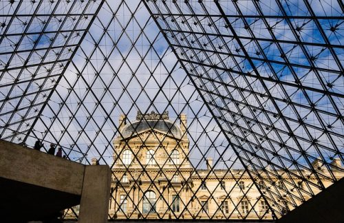 Pirâmide transparente e arquitetura ao fundo, em Paris