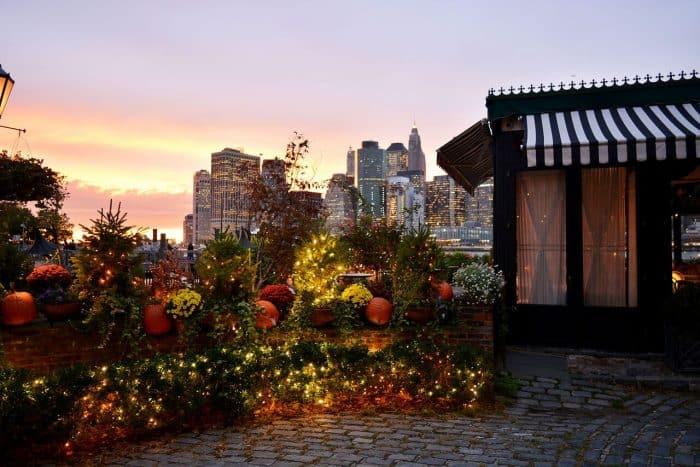 Casa com jardim e prédios iluminados ao fundo
