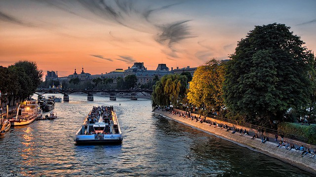 turistas passeando de barco pelo Rio Sena ao entardecer