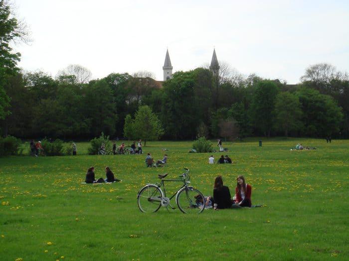 pessoas em um gramado, com torres ao fundo