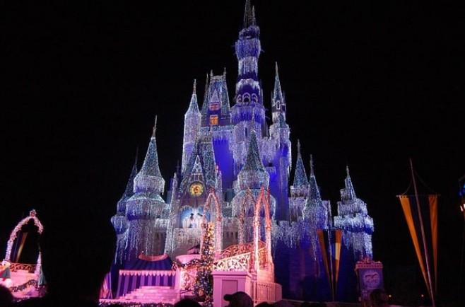 Magic Kingdom: Castelo da Cinderela com luzes coloridas iluminando de noite