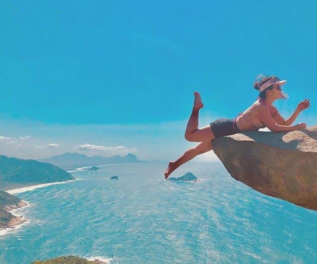 Turista na ponta da pedra e praia ao fundo