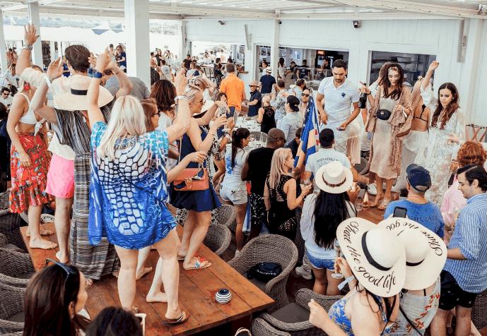 pessoas dançando sobre mesas, em praia