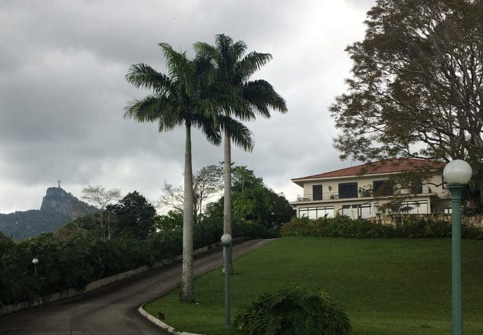 Jardins com Cristo e casa ao fundo