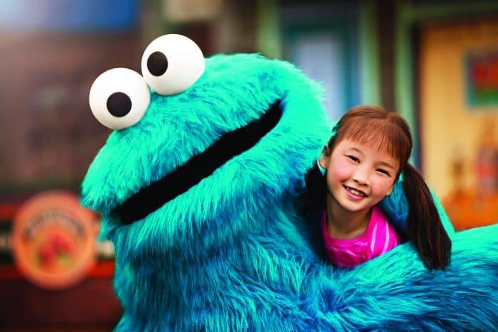 Criança abraçando boneco azul