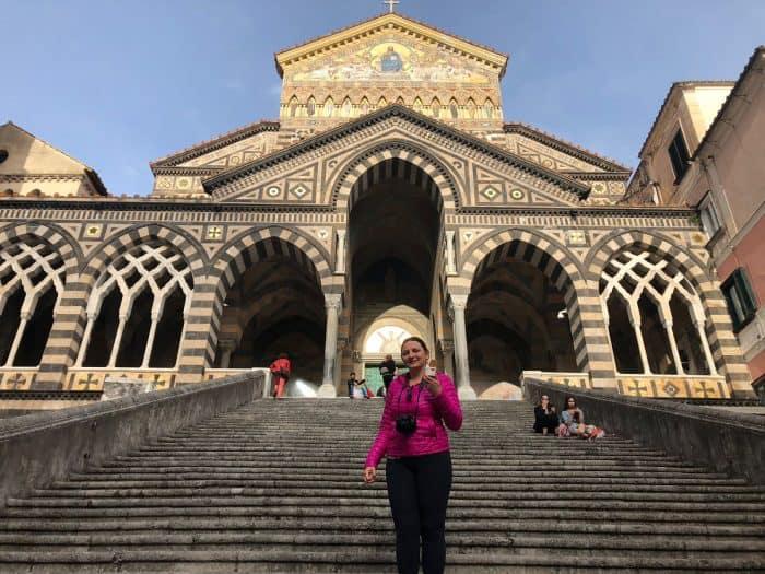 Frente de igreja em Amalfi e turista na escada