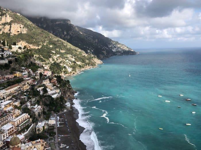Casas em montanhas e mar com diferentes tons de azul