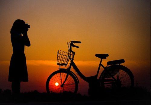 Mulher tirando foto ao lado de bicicleta