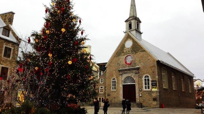 Igreja pequena feita de pedras de frente para árvore de natal