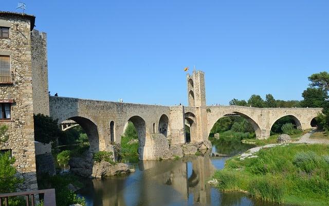 Muralhas de pedra com arcos inferiores, sobre um rio em Girona