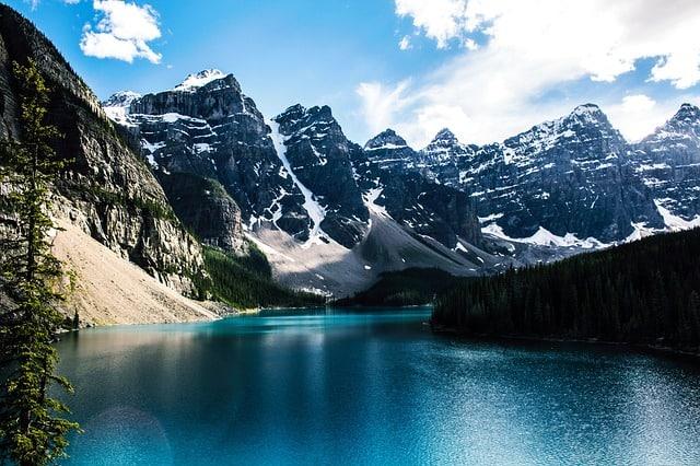 Lago azul no meio de pequenas montanhas com neve no cume