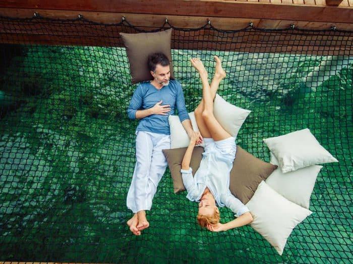 Casal deitado em rede transparente sobre o mar