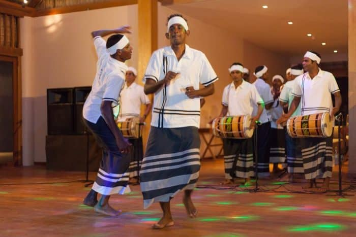 Pessoas dançando e cantando em salão das Maldivas