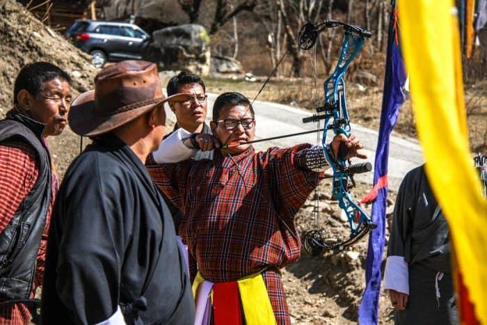 Homem com arco e flecha em mãos em estrada