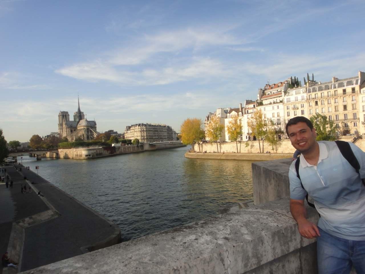 Turista em foto com o Rio Sena e a Notre Dame ao fundo