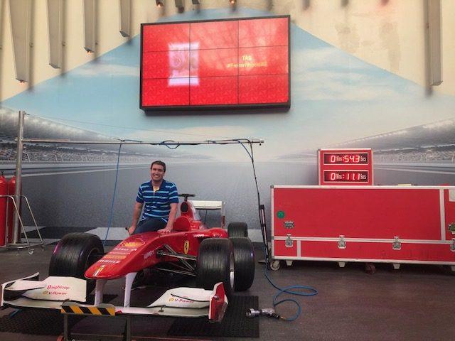 Turista tira foto sentado em uma Ferrari da Fórmula 1