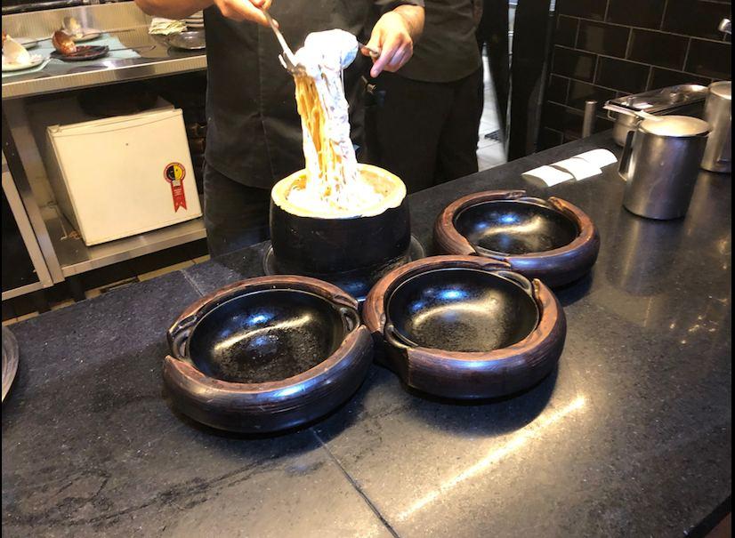 Chef prepara macarrão dentro de um queijo parmesão