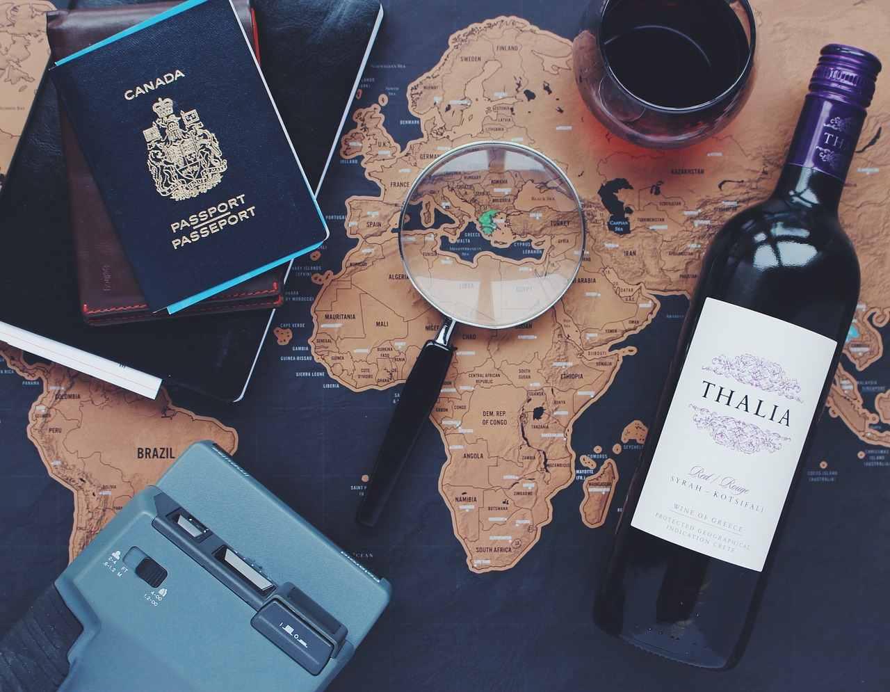passaporte, garrafa de vinho, lupa e o mapa para tirar a próxima viagem do papel